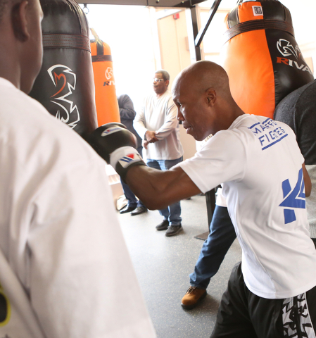 Boxer Zab Judah, right, gives a lesson on how to use a heavy punching bag to a young boxer at the Spring Mountain Youth Camp Wednesday, April 22, 2015.  Professional boxers and boxing referees vis ...