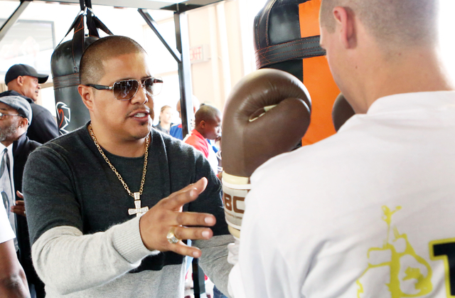 Boxer Fernando Vargas, left, gives boxing lessons to a young boxer at the Spring Mountain Youth Camp Wednesday, April 22, 2015. Professional boxers and boxing referees visited the camp, where youn ...