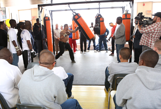 Youth watch as boxer Jessie Vargas, center, gives lessons on how to use a heavy punching bag to young boxers, left, at the Spring Mountain Youth Camp Wednesday, April 22, 2015. Professional boxers ...