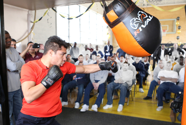 Youth watch as boxer Jessie Vargas gives a lesson on how to use a heavy punching bag at the Spring Mountain Youth Camp Wednesday, April 22, 2015. Professional boxers and boxing referees visited th ...