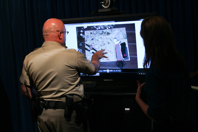 Las Vegas police officials look over images before Undersheriff Kevin McMahill addresses news media about an officer-involved shooting that took place April 29, at Las Vegas police headquarters on ...