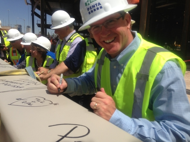 Tim Romani, president of Denver-based ICON, the arena construction management company overseeing the project, signs the final steel beam of the $375 million arena being built by MGM Resorts Intern ...
