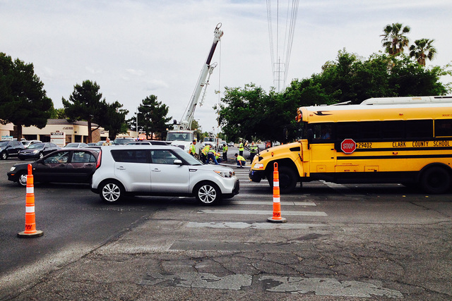Clark County traffic signal technicians work at the corner of Pecos Road and Harmon Avenue to replace a traffic light damaged in a two-vehicle crash on Wednesday, May 13, 2015. Southbound lanes on ...