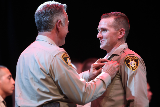 Clark County Sheriff Joe Lombardo, left, places a police badge on the uniform of police academy graduate Russell Buchanan during the Las Vegas Metropolitan Police Department graduation ceremony fo ...