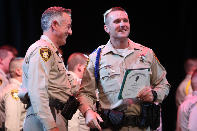 Clark County Sheriff Joe Lombardo, left, looks on after awarding a police badge to police academy graduate Russell Buchanan during the Las Vegas Metropolitan Police Department graduation ceremony  ...