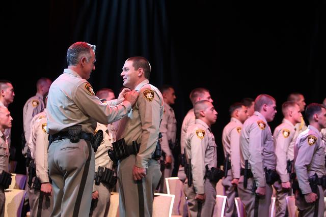 Clark County Sheriff Joe Lombardo, left, places a police badge on the uniform of police academy graduate Joshua Conte during the Las Vegas Metropolitan Police Department graduation ceremony for th ...