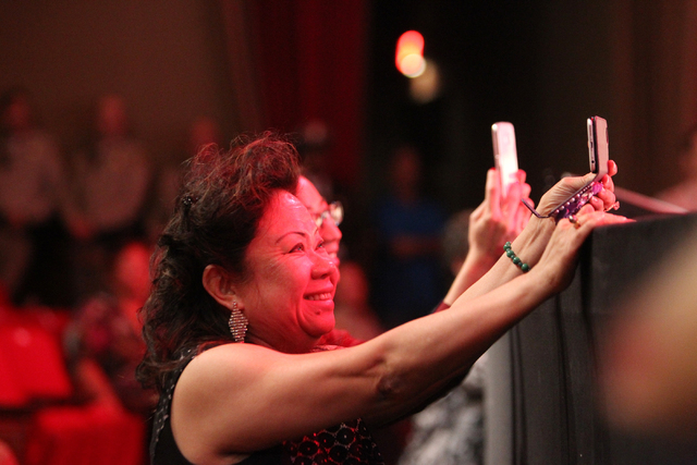An unidentified woman photographs police academy graduate Christopher Dihn during the Las Vegas Metropolitan Police Department graduation ceremony for the class of 11-2014 at the Orleans casino-ho ...