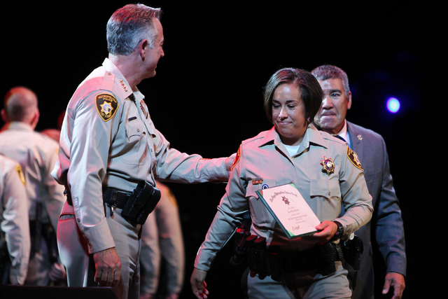 Tana Gurule, right, sheds a tear after receiving her new police officer badge and certification from Clark County Sheriff Joe Lombardo, left, during the Las Vegas Metropolitan Police Department gr ...
