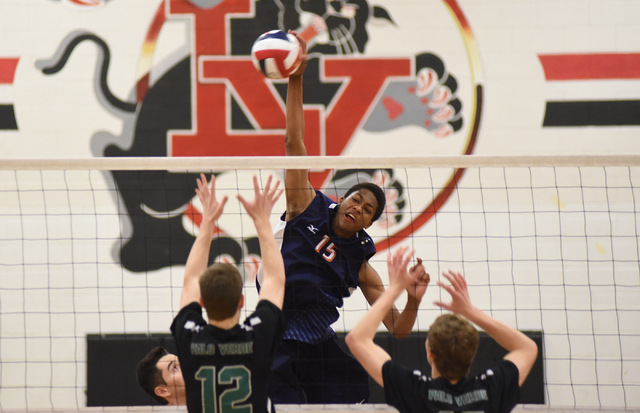 Legacy's Omari Wheeler (15) spikes the ball against Palo Verde's Chandler Juilfs (12) during their Division I state volleyball final inside the Las Vegas High School gym in Las Vegas on Wednesday, ...