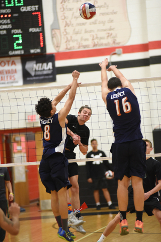 Palo Verde's Parker Nelson (6) spikes the ball against Legacy's Anthony Guevara (8) and Jonathan Shawkey (16) during their Division I state volleyball final inside the Las Vegas High School gym in ...