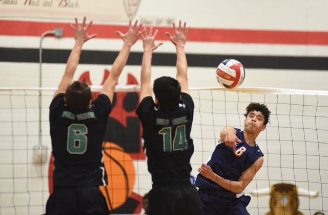 Legacy's Anthony Guevara (8) spikes the ball against Palo Verde's Parker Nelson (6) and Tristan Bradford (14) during their Division I state volleyball final inside the Las Vegas High School gym in ...
