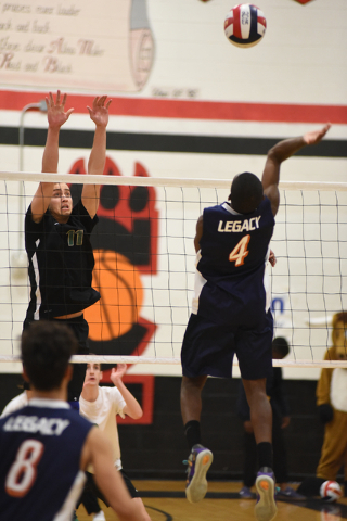 Legacy's Zaire Franklin (4) spikes the ball against Palo Verde's Michael Simister (11) during their Division I state volleyball final inside the Las Vegas High School gym in Las Vegas on Wednesday ...