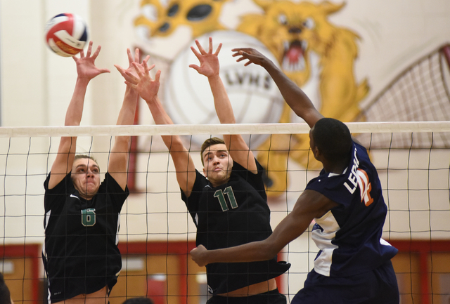 Legacy's Zaire Franklin (4) spikes the ball against Palo Verde's Parker Nelson (6) and Michael Simister (11) during their Division I state volleyball final inside the Las Vegas High School gym in  ...