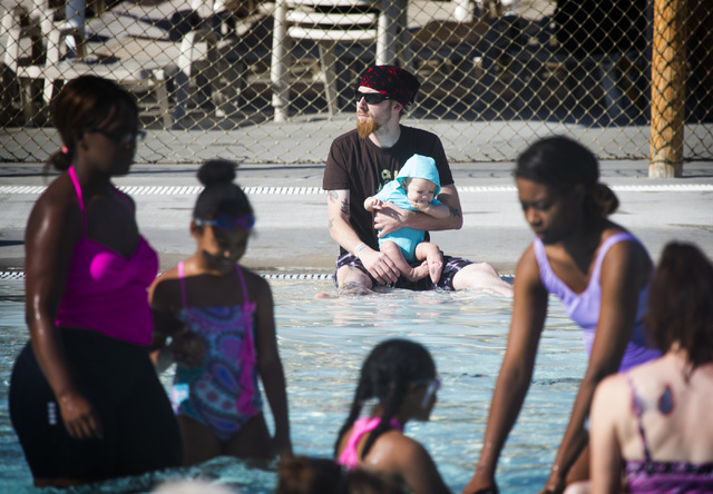 Eric Clarke holds his son Max during a swimming class at Wet'N'Wild Las Vegas June 20, 2014. The theme park participated in the world's largest simultaneous swimming lesson. (Jeff Scheid/View file ...