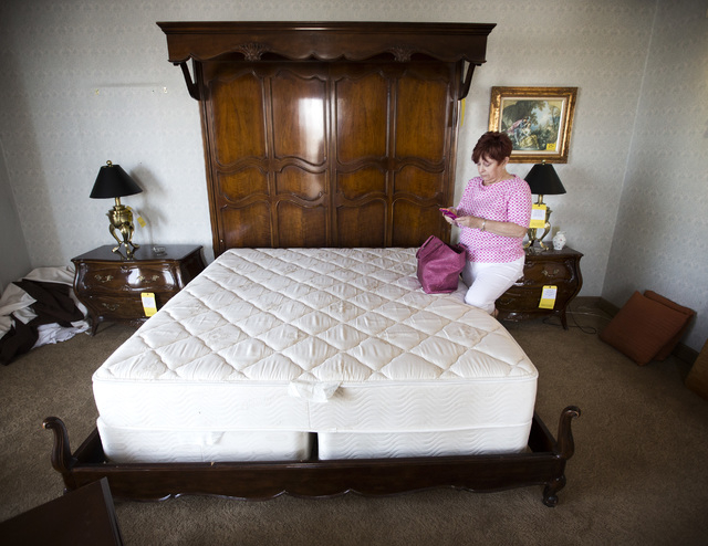 Long time former Riviera employee Barbara Kindt texts a friend while she stand in the master bedroom  in the Frank Sinatra suite during the liquidation sale at the closed Riviera hotel-casino, 290 ...