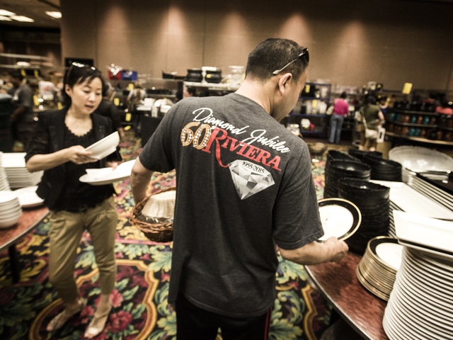 Former Riviera dealer Richard B., declined to give last name, and Rufina Cao looks at plates during the liquidation sale at the closed Riviera hotel-casino, 2901 South Las Vegas Boulevard on Wedne ...
