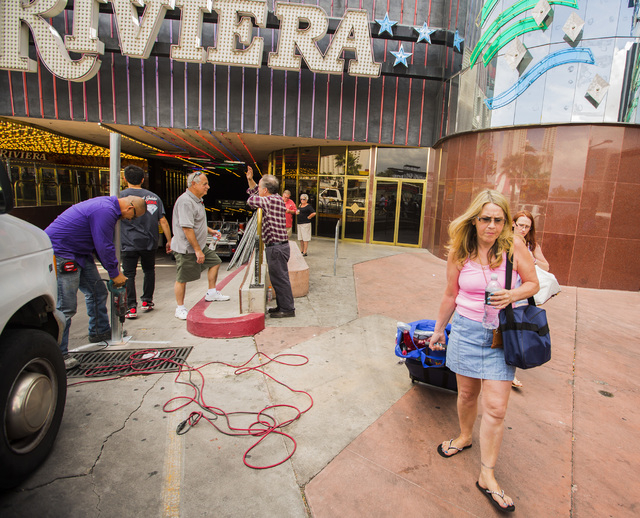 People leave the the Riviera hotel-casino while construction crews erect fencing on Monday, May 4, 2015. The casino closed Monday after 60 years on the Las Vegas Strip. (Jeff Scheid/Las Vegas Revi ...