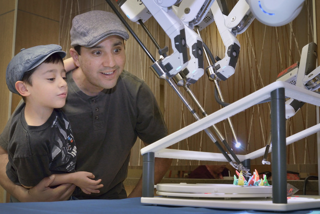 Leonardo Gutierrez, left, 5, and his father, Daniel, watch the da Vinci Xi robotic surgical system in operation at Mountain View Medical Center at 3100 N. Tenaya Way in Las Vegas on Saturday, Apri ...