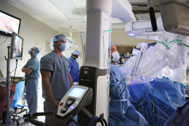 Surgeon Dr. Shawn Tsuda, right, looks up at a monitor while he assists and supervises in a gallbladder removal surgery using robotics on patient Jenilee Lemunge, covered at right, at University Me ...