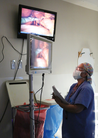 Carmen Reyes-Vaquero, registered nurse, looks at live video of a hernia repair surgery using robotics on patient Jenilee Lemunge at University Medical Center Wednesday, May 20, 2015, in Las Vegas. ...