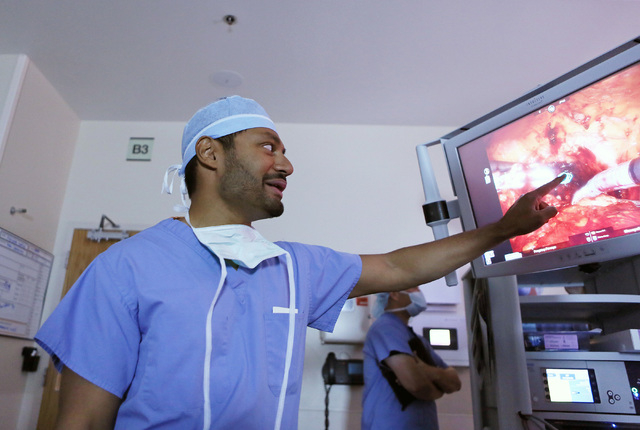 Urologic surgeon Dr. Jayram Krishnan takes a brief break from performing bladder reconstruction on a cancer patient to explain actions on a monitor in the operating room at Sunrise Hospital & Medi ...