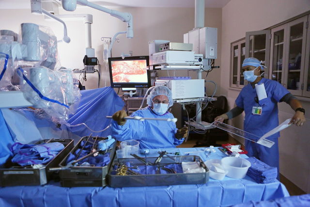 Scrub nurse and surgical technician James Ploudre, center, receives assistance with surgical robotic tools from nurse Edward Gravidez during a robotic bladder reconstruction procedure on a cancer  ...