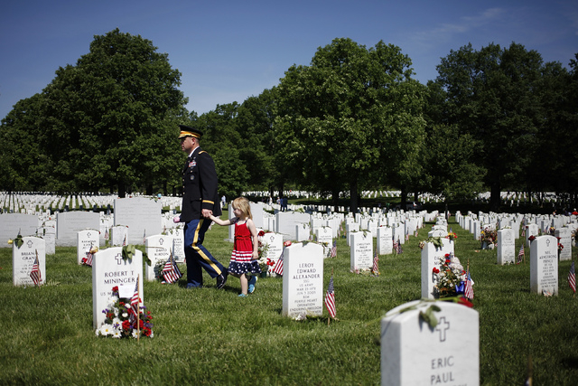 Visitors walk between graves in Section 60, where many casualties of the U.S. wars in Iraq and Afghanistan are buried, on Memorial Day at Arlington National Cemetery in Arlington, Virginia May 26, ...