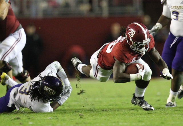 Alabama Crimson Tide running back Altee Tenpenny (28) is tripped up by Western Carolina Catamounts defensive back Fred Payne (3) at Bryant-Denny Stadium in Tuscaloosa, Ala., on Nov. 22, 2104. The  ...