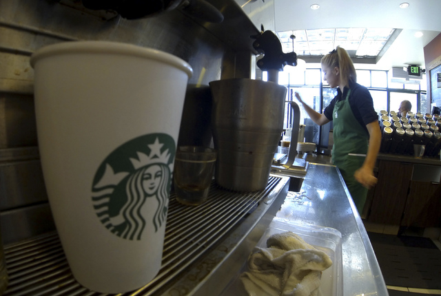 A barista makes drinks inside a newly designed Starbucks coffee shop in 2013.  (Mike Blake/Reuters)