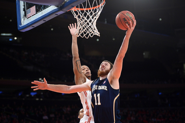 Dec 21, 2013; New York, NY, USA; Notre Dame Fighting Irish center Garrick Sherman (11) puts up a layup over Ohio State Buckeyes center Amir Williams (23) during the first half of the Gotham Classi ...