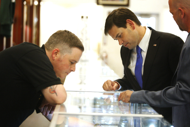 Numismatist Mike Long, left, and Rick Harrison, right, co-owner of World Famous Gold & Silver Pawn Shop, give a tour to Republican presidential candidate U.S. Sen. Marco Rubio,  R-Fla., at the Wor ...