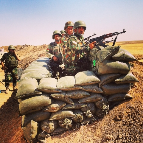 Kurdish fighters pose for cameras at a frontline position west of Erbil. After a panicked retreat last Wednesday, the Kurds have regrouped and are digging in...fortifying their defenses. Their com ...