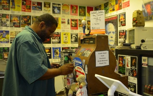 William Powell adjusts magnets on a vintage cash register inside The Sci Fi Center. (Ginger Meurer/Special to View)