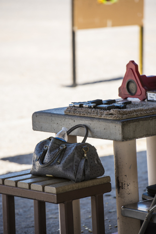 A designer purse rests near a table with handguns at the Clark County Shooting Complex May 17, 2015. (Joshua Dahl/View)