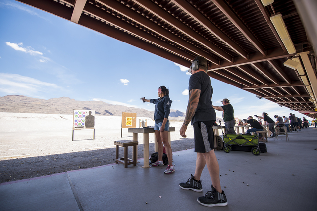 Dana Dwiggins takes shots with a handgun as Joel Powell looks on at the Clark County Shooting Complex May 17, 2015. (Joshua Dahl/View)