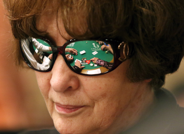 A World Series of Poker dealers motions can be seen reflected in sunglasses worn by poker player Yvonne Brasfield during the Casino Employees No-Limit Holdem event at Rio hotel-casino Wednesday, M ...