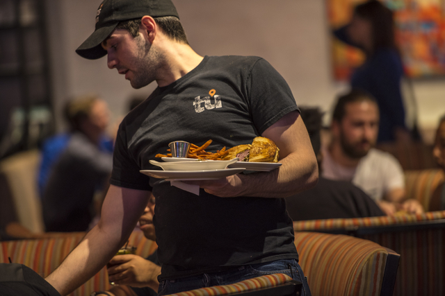 A server brings out food at Tom's Urban inside New York-New York in Las Vegas on Saturday, May 23, 2015. (Joshua Dahl/Las Vegas Review-Journal)