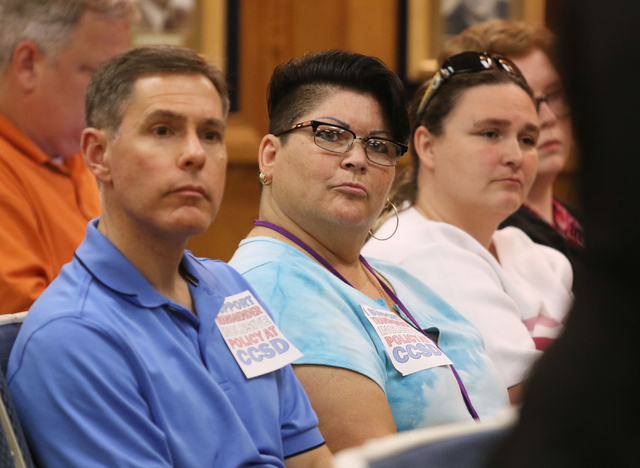Deb Bartholme, center, looks at a speaker during public comment at a Clark County School Board meeting Thursday, May 28, 2015, in Las Vegas. Bartholme, as well as Rich Moorehead, left, wear sticke ...