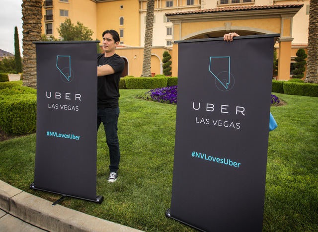 Uber marketing manager Kris Cuaresma-Primm removes signs after a press conference at the Hilton Lake Las Vegas Resort, 1610 Lake Las Vegas Parkway in Henderson on Wednesday, March 18, 2015. Repres ...