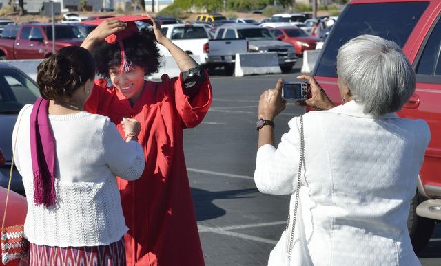 Valerie Reives (cq), center, gets some help from her mother Cecilia Reives, left, as her grandmother Evelyn Reives takes a photo before UNLV graduation ceremonies at the Thomas & Mack Center at 45 ...
