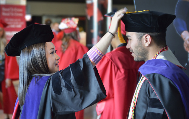 Law student Christina Connolly helps fellow law student Robert Loftus adjust his cap during UNLV graduation ceremonies at the Thomas & Mack Center at 4505 S. Maryland Parkway in Las Vegas on Satur ...