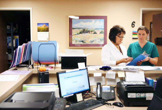 Registered nurse Agnes Escalona, left, instructs new volunteer Meghan Bell, also an R.N., at Volunteers in Medicine of Southern Nevada, 4770 Harrison Drive, in Las Vegas, Friday, Sept. 7, 2012. Th ...