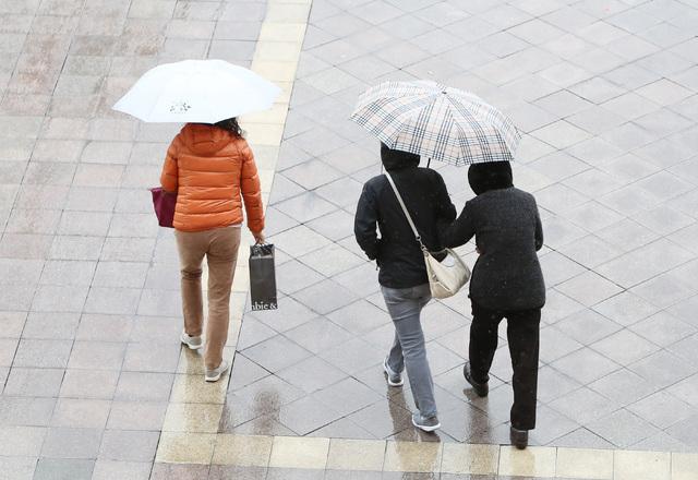 Pedestrians holding umbrellas walk on the side walk along Las Vegas Boulevard near Venetian Friday, Jan. 30, 2015. (Bizuayehu Tesfaye/Las Vegas Review-Journal)