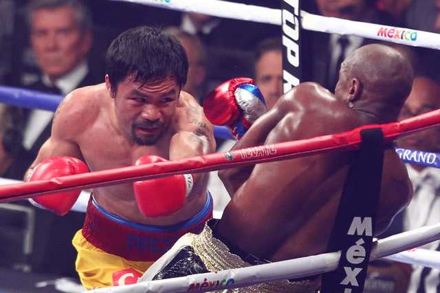 Floyd Mayweather Jr., right, dodges a punch from Manny Pacquiao in their welterweight unification boxing match at the MGM Grand Garden Arena in Las Vegas on Saturday, May 2, 2015. (Chase Stevens/L ...