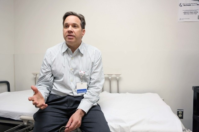 Dr. Jay Fisher, medical director of pediatric emergency services at UMC Children's Hospital of Nevada, sits on a bed in a mental health evaluation room and speaks about pediatric mental health in  ...