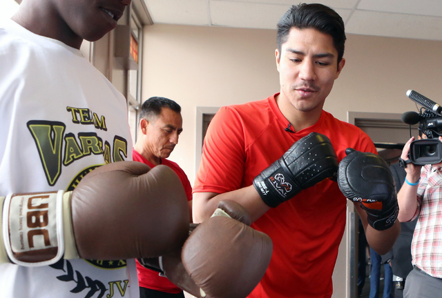 Boxer Jessie Vargas, right, gives boxing lessons to a young boxer at the Spring Mountain Youth Camp Wednesday, April 22, 2015.   Professional boxers and boxing referees visited the camp, where you ...