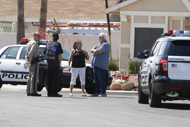 A metro police officer talks to area residents near the house where two people were wounded in a northwest valley shooting on Thursday, May 7, 2015 at the 5800 block of Westport Circle, near the i ...