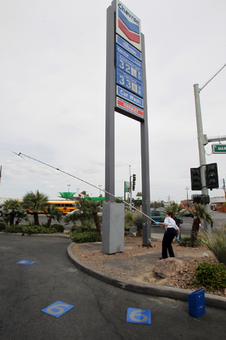 Becky Fichter, store manager at Terrible's at Martin Luther King Boulevard and Bonanza Road, struggles against the wind to change the gas price on the sign on Wednesday, May 13, 2015. The prices w ...