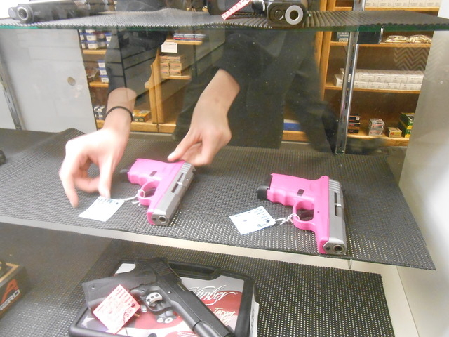"Rachel Richards puts a pink gun back in a showcase at The Gun Store Jan. 26, 2015. She said that when women come in to buy a gun, they don't stipulate they be served by a man or a woman. ""They jus ..."