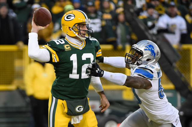 Dec 28, 2014; Green Bay, WI, USA;  Green Bay Packers quarterback Aaron Rodgers (12) gets a pass away from Detroit Lions linebacker Tahir Whitehead (59) in the second quarter at Lambeau Field. (Ben ...
